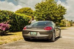 Possibilité éloignée d'un jeune homme au téléphone, se tenant prêt un banc de sable de Porsche photo stock