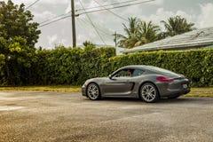 Possibilité éloignée d'un jeune homme conduisant Porsche Cayman Scène urbaine image libre de droits