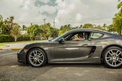 Possibilité éloignée d'un jeune homme conduisant Porsche Cayman Scène urbaine photos stock
