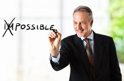 Possible. Motivation concept. Businessman changing the word impossible into possible Royalty Free Stock Photography