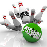 Possible Bowling Ball Strike Impossible Pins Achieving Goal. A green bowling ball with the word Possible hits a strike in pins marked Impossible to prove Stock Photography
