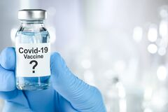 Possible cure with a hand in blue medical gloves holding Coronavirus, Covid 19 virus, vaccine vial