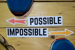 Possible or Impossible opposite direction signs with sneakers and eyeglasses on wooden royalty free stock photo