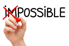 Possible Not Impossible. Hand turning the word Impossible into Possible with red marker isolated on white Royalty Free Stock Images