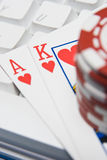 Possible royal flush?. Online gambling with an ace and a king with a keyboard and chips royalty free stock photo