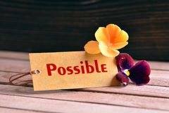 Possible tag. Tag banner possible and violet flower on wooden desk Royalty Free Stock Photo