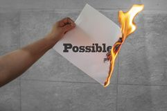 Possible text word on fire with paper burning. In hand stock image