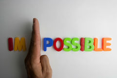 Possible. The word Im - Possible on a line  blocks separated by the hand Stock Photo