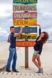 possing在方向的一个人和红头发人女孩竖立路标 库存图片