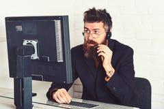 Posso lo aiuto Rispondendo le chiamate dai clienti Operatore della call center sul lavoro Uomo barbuto che lavora nell'ufficio Uo immagine stock