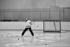 Postérieur des galets d'un tir d'homme sur un filet d'hockey Photos stock