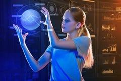 Postępowa dziewczyna trzyma hologram i patrzeje je zdjęcia stock