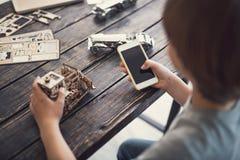 Postępowy chłopiec obsiadanie przy stołem z drewnianym konstruktorem na nim i mienia nowożytnym smartphone w jego ręki obrazy stock