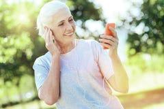 Postępowy energiczny emeryt używa jej smartphone obrazy royalty free