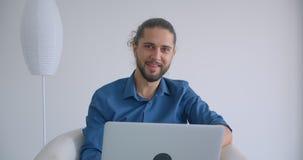 Postępowy freelancer z ponytail pracuje z laptopu obsiadaniem w karle w wygodnych i lekkich biurowych uśmiechach w zbiory wideo