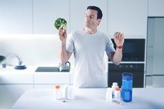 Postępowy mężczyzna ma mnóstwo medicaments i patrzeje brokuły zdjęcia stock