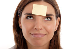 Post-it. Stock photo of a young pretty woman with a post-it note on her forehead stock images