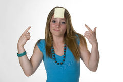 Post-it. Yellow post-it stuck on teenage girl's forehead Royalty Free Stock Image