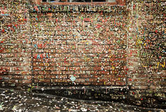 Post Alley Walls With Gum. An old brick wall in Post Alley in the Pike Place Market in Seattle is covered with chewing gum deposited over a number of years. The Stock Image