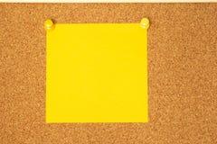 Post-it amarillo en un fondo del coarkboard Imagenes de archivo