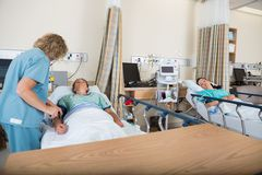 Post Anesthesia Care Unit. Mature nurse examining patient in post anesthesia care unit Royalty Free Stock Photo