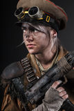 Post apocalypse female survivor. Nuclear post apocalypse life after doomsday concept. Grimy female survivor with homemade weapons. Studio portrait on black Royalty Free Stock Image