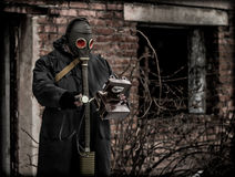 Post apocalypse and pollution concept.Man in a gas mask. Man in a gas mask, a grey cloak and with a Geiger counter walking on destroyed city ruins and measures Royalty Free Stock Photography