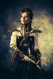 Post-apocalypse. Portrait of a beautiful steampunk woman over grunge background Stock Photos