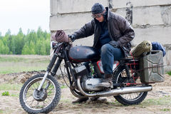 A post apocalyptic man on motorcycle near the destroyed building Stock Photography