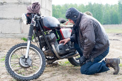 A post apocalyptic man on motorcycle near the destroyed building Stock Images