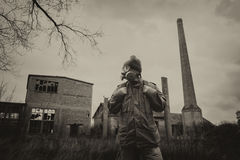 Post apocalyptic survivor in gas mask and backpack. Walking through devastated civilization royalty free stock images