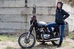A post apocalyptic woman near motorcycle near the destroyed building. A post apocalyptic woman near motorcycle near destroyed building stock images