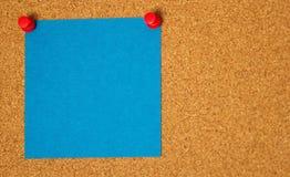 Post-it azul en un fondo del coarkboard Foto de archivo libre de regalías