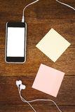 Post it and black smartphone with white headphones Royalty Free Stock Photo