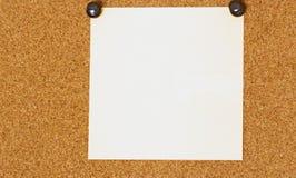 Post-it blanco en blanco en un fondo del coarkboard Fotografía de archivo libre de regalías