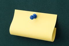 Post-it with blue pushpin. Yellow post-it note with blue pushpin on green board Royalty Free Stock Photos