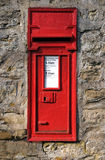 Post box. UK red post box fixed into a stone wall royalty free stock photography