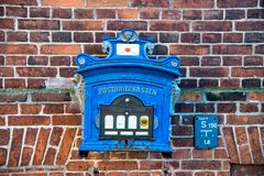 Post box of blue painted metal on red brick wall Royalty Free Stock Photos