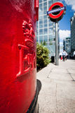 Post box detail. Close-up on red post box in London, near an Underground sign in the Docklands Stock Image