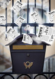 Post box with daily newspapers flying Royalty Free Stock Images