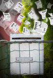 Post box with daily newspapers flying. Out Stock Images