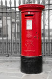 Post box. Red uk traditional post box next to the fence stock images