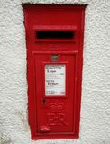 Post box on wall. Red postbox on the white wall at Alnmouth England, taken on 15th August 2017n Royalty Free Stock Image