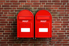 Post boxes. Two red post boxes on a brick wall Royalty Free Stock Images