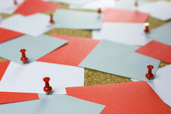 Post-it bulleting board. A bulletin cork board background with messy square pieces of white, blue and red posting paper, red pins Stock Image