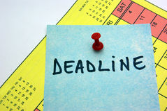 Post it on calendar. Deadline post it on a yellow calendar Royalty Free Stock Photo