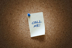 Post-it with call me message. Post-it with message on corkboard Royalty Free Stock Images