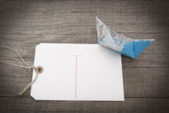 Post card with a boat folded out of map and a wooden background Royalty Free Stock Image