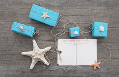 Post card with a starfish and turquoise gifts and a wooden backgr Stock Image