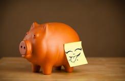 Post-it con il fronte sorridente sticked sul porcellino salvadanaio Fotografia Stock Libera da Diritti